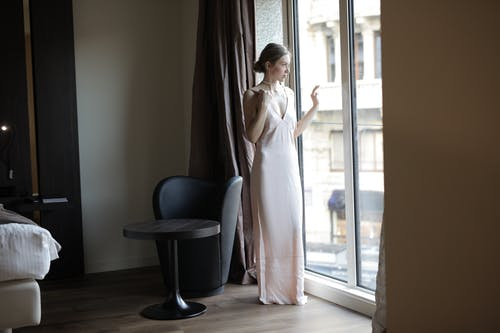 Woman in White Dress Standing Near Window