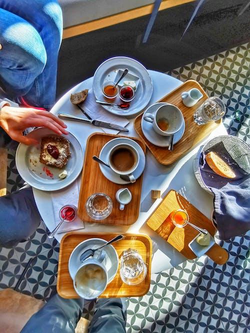 Crop people having breakfast in modern cafe