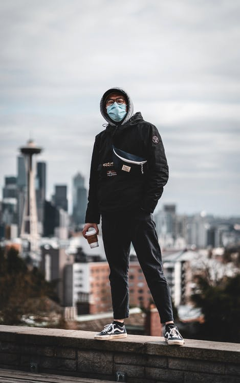Trendy ethnic man in mask standing on rooftop in city