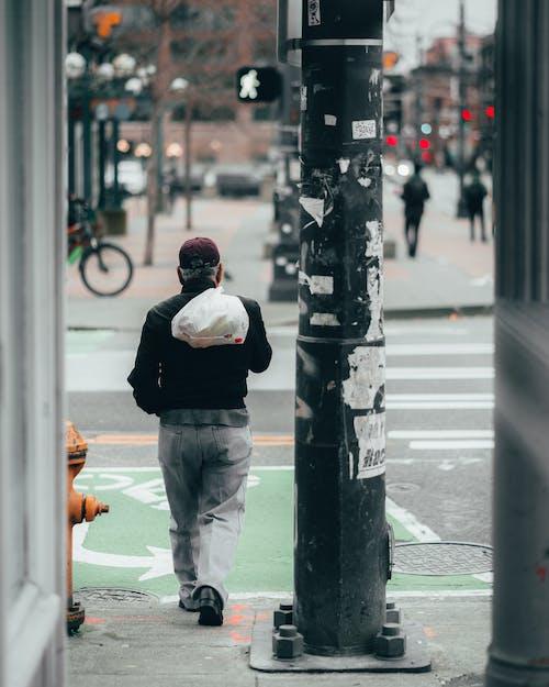 Man In Black Jacket And Gray Pants Walking On Sidewalk