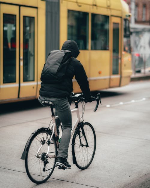 Man In Black Jacket Riding A Bicycle