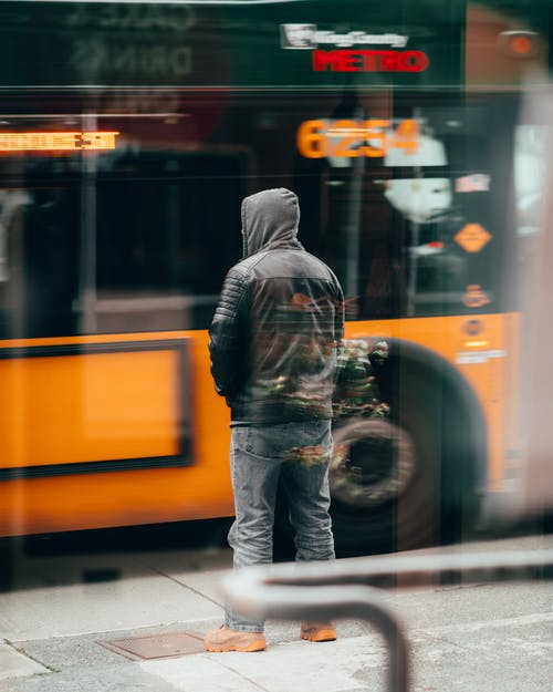 Man In Black Jacket And Blue Denim Jeans Standing In Front Of Yellow Bus