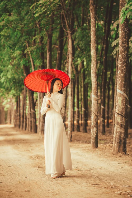 Woman In White Dress Holding Red Umbrella