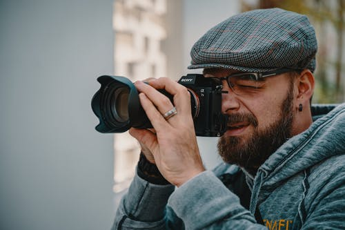 Man in Blue Denim Jacket Holding Black Dslr Camera