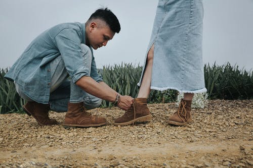 Man In Denim Top And Blue Denim Jeans Tying Woman's Shoe Lace