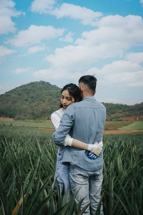 Man In Denim Long Sleeve Shirt Hugging Woman