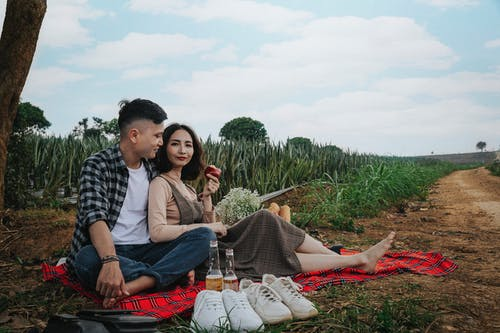 Man And Woman Sitting On Red Textile Having A Picnic