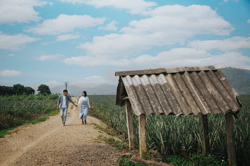 Man And Woman Walking On Dirt Road Near Green Grass Field Under White Clouds