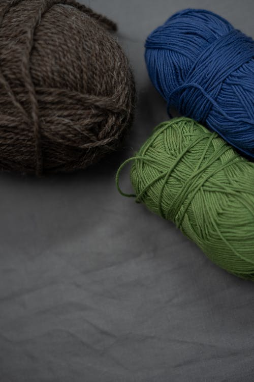 Blue and Green Yarn on White Textile