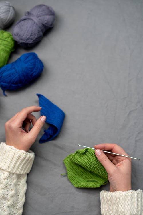 Person Holding Blue Textile and White Yarn