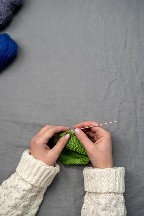 Person Holding Green and White Textile