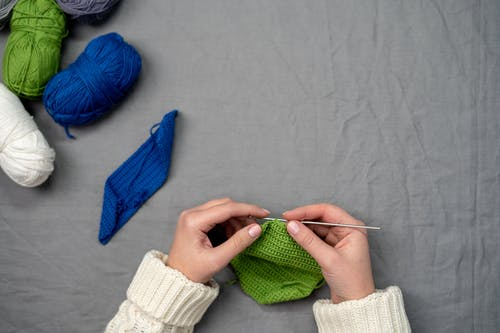 Person Holding Green Knit Textile