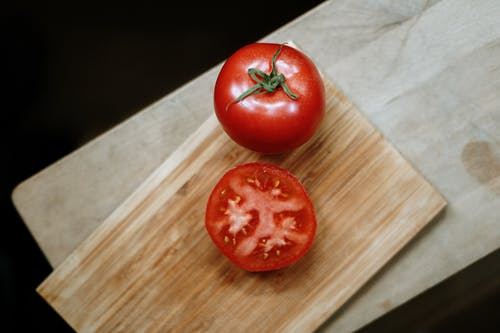 Red Tomato On Brown Wooden Chopping Board