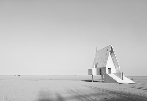 Grayscale Photo of Wooden House On The Beach