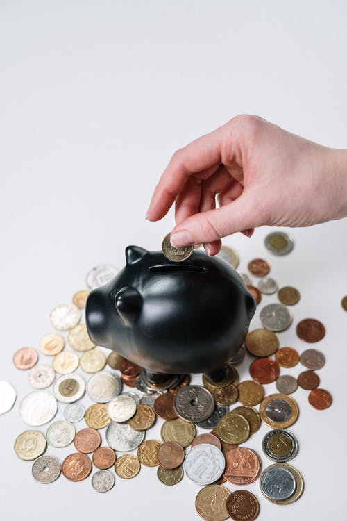 Person Holding Black Ceramic Coin Bank