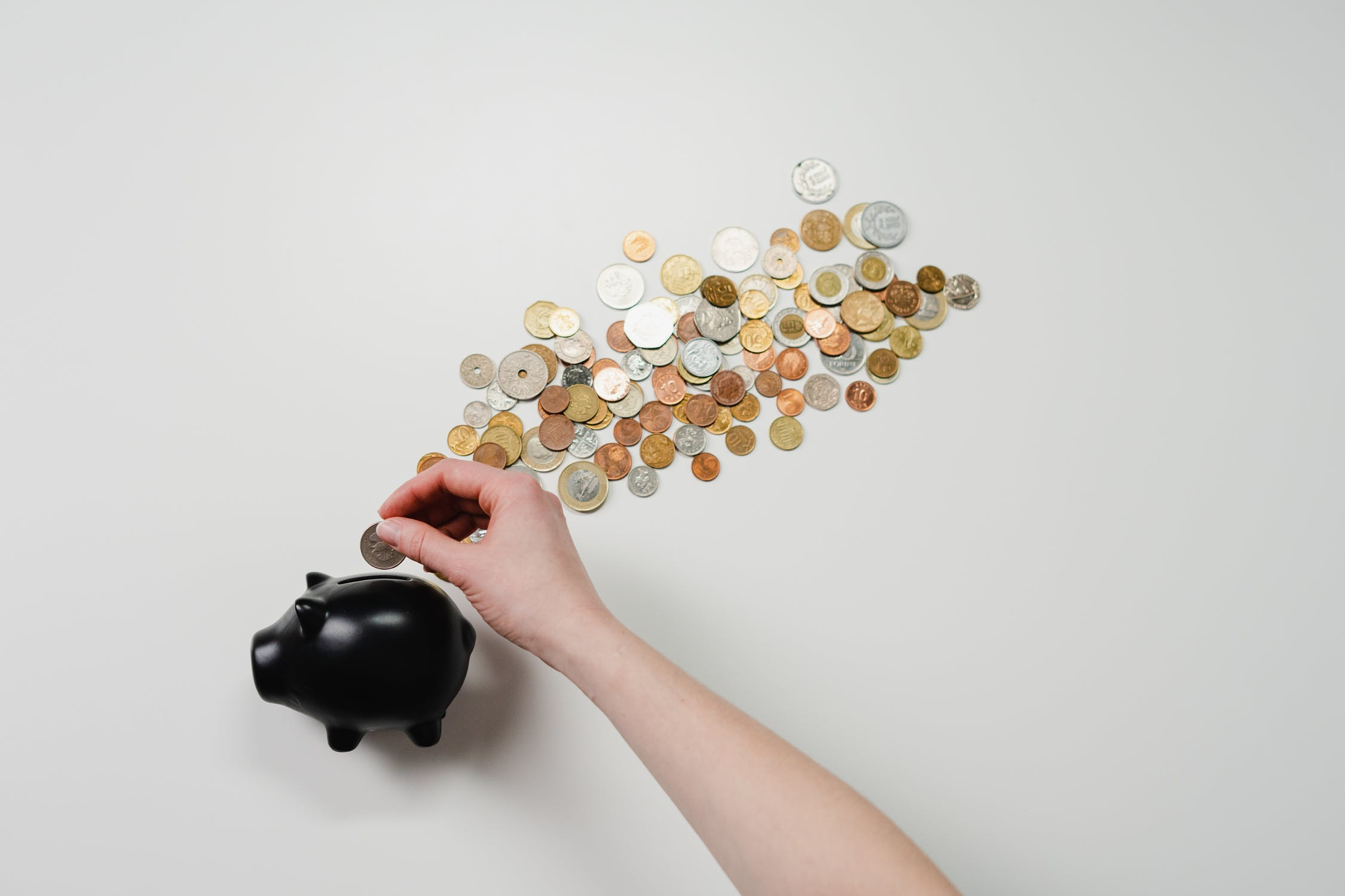 Image of black piggy bank surrounded by coins, demonstrating business savings from chatbot marketing