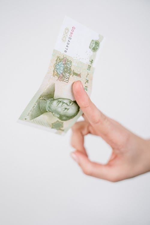 Person Holding 20 Banknote on White Surface