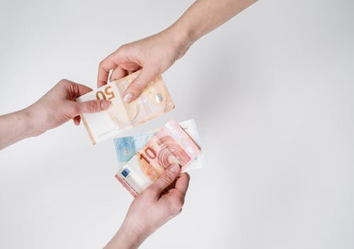 Person Holding 10 and 10 Euro Banknotes
