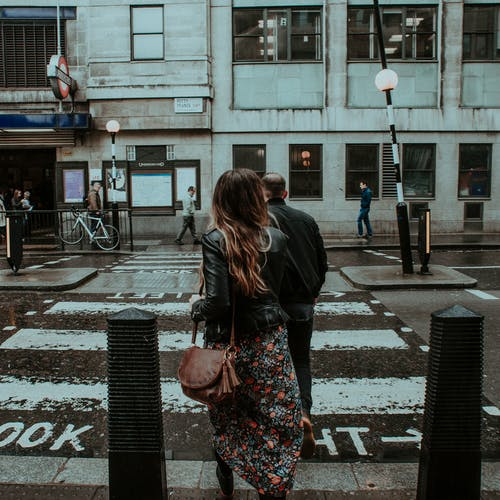 Woman in Black Jacket Crossing on Sidewalk