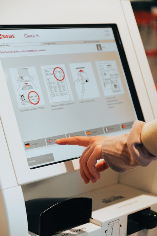Person in Brown Long Sleeve Shirt Using Self Service Check in Kiosk