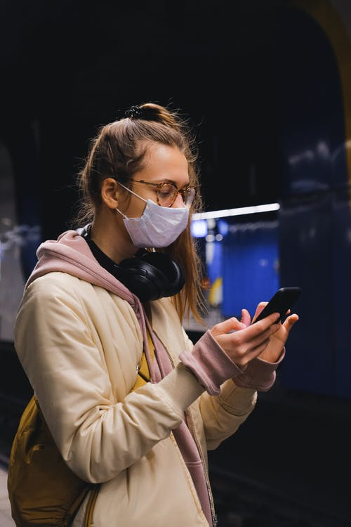 Woman With a Face Mask Using a Smartphone