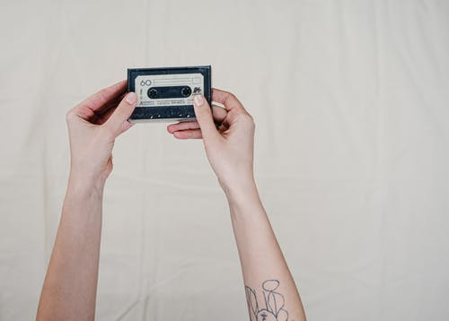 Person Holding Black and Gray Cassette Tape
