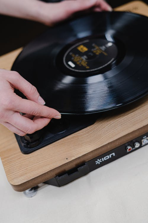 Person Holding Vinyl Record On Vinyl Record Player