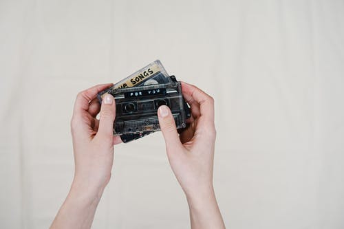 Person Holding Black Cassette Tape