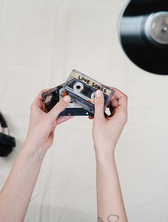 Person Holding Blue and Black Cassette Tape
