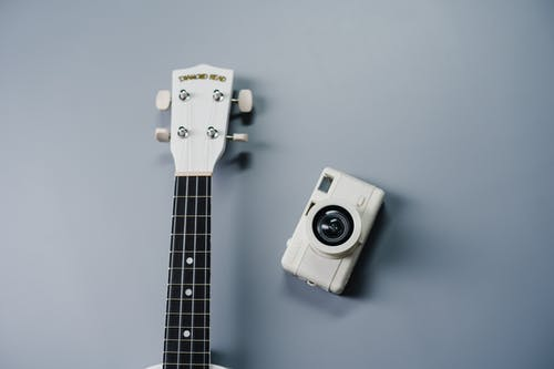 White and Black Camera on White Guitar