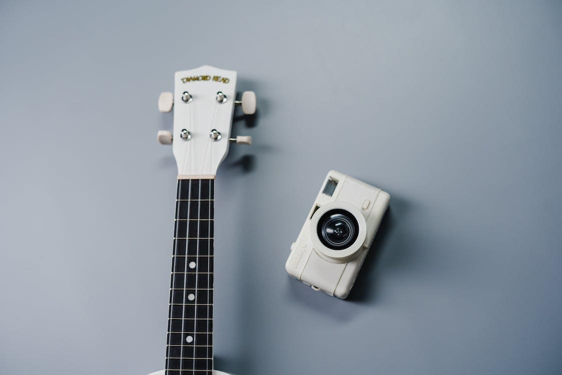 White and Black Camera on White Guitar