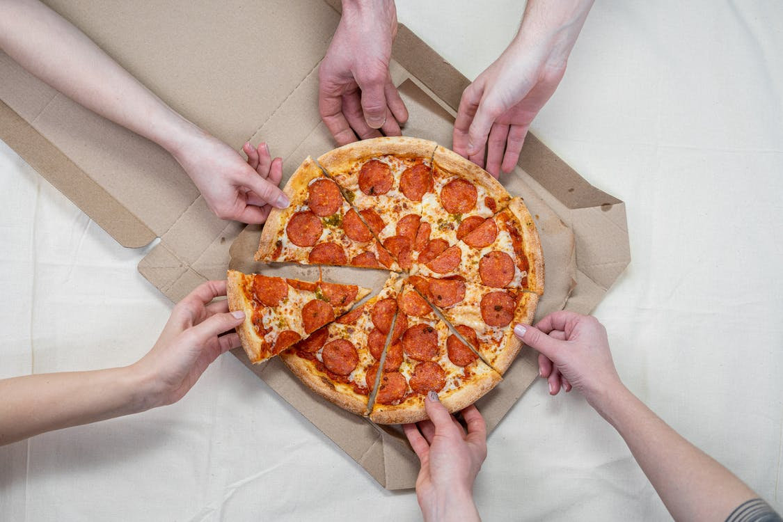 Person Holding a Pizza With Cheese