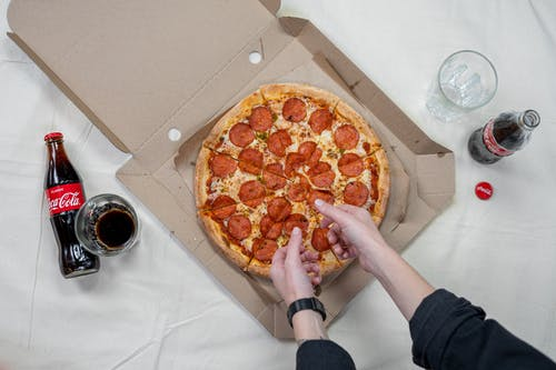 Person Holding Pizza With Cheese