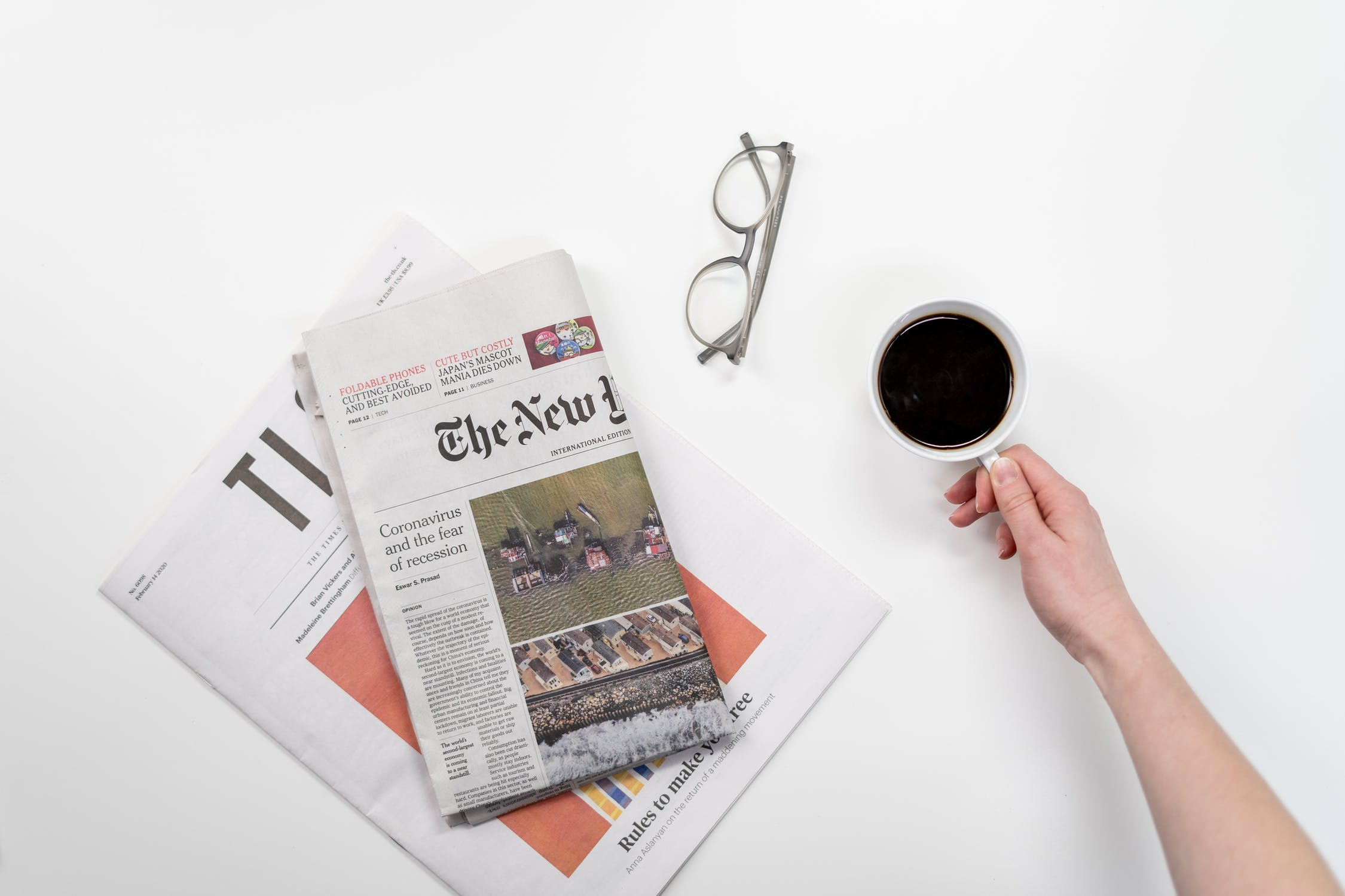 A picture of a table with stacked newspapers, a cup of coffee, and a folded up pair of glasses