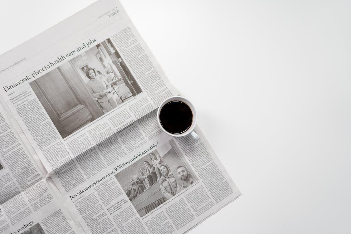White Ceramic Mug On Top Of A Newspaper