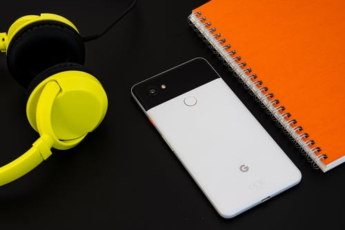 Mobile Phone Beside Notebook And Headphones