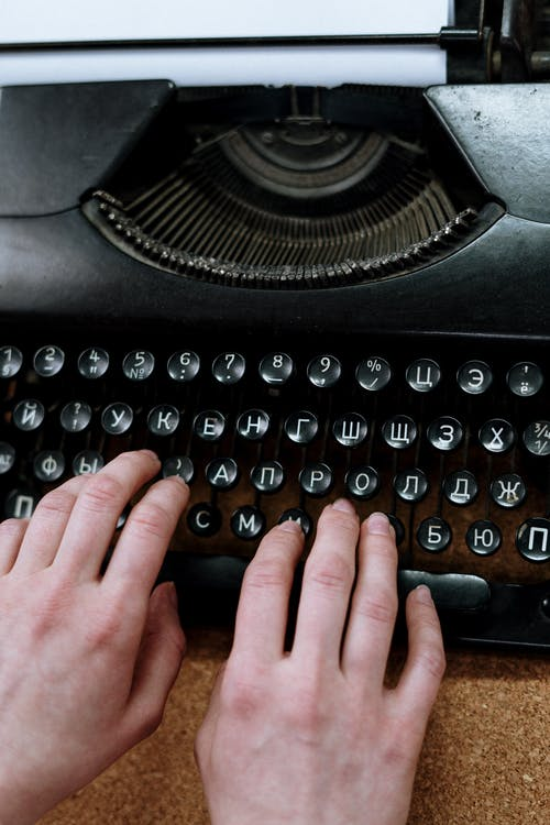Persons Hand on Typewriter