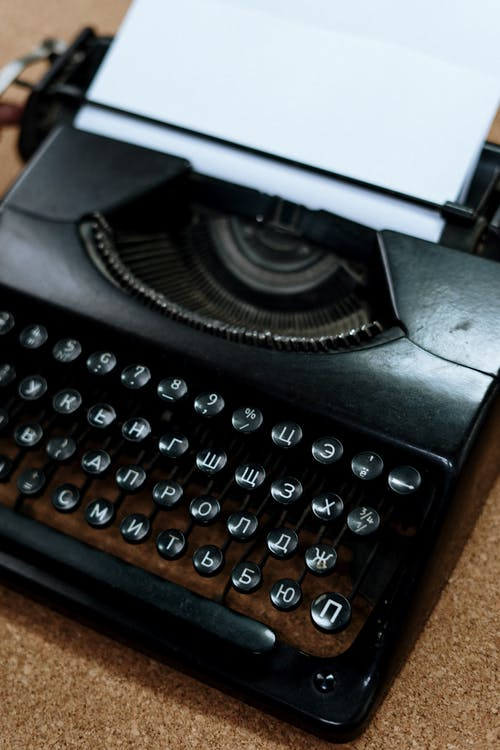Black Typewriter on Brown Wooden Table