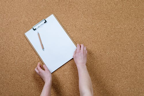 Person Holding White Paper on Brown Carpet
