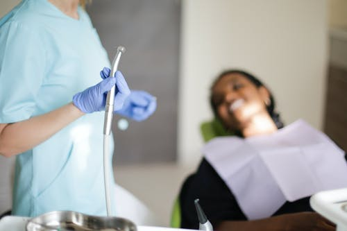 Woman in Blue Scrub Suit and Latex Gloves Holding Stainless Teeth Cleaner Machine
