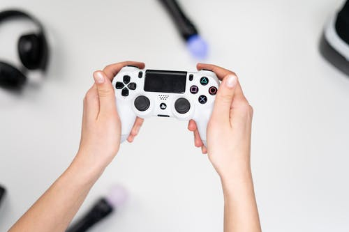 Person Holding Gray and Black Sony Ps 4 Controller