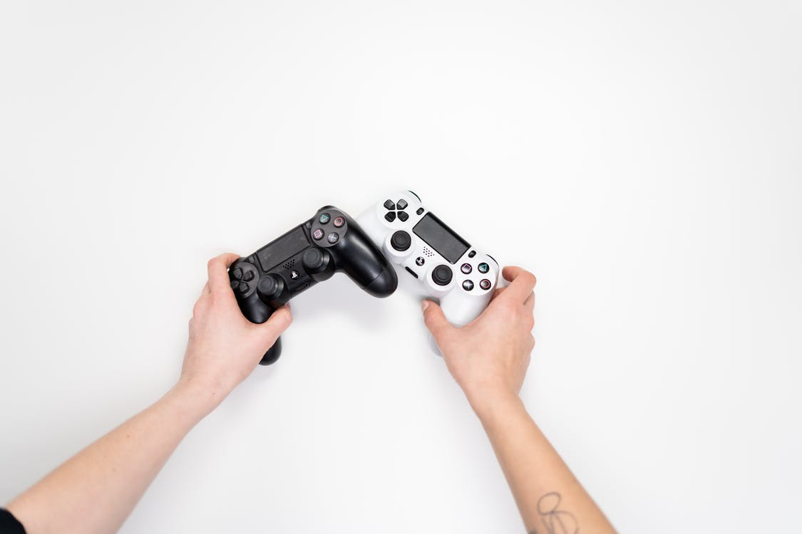 Person Holding Black and White Sony Ps 4 Controller