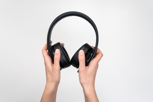 Person Holding Black Wireless Headphones
