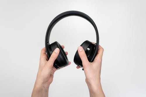 Person Holding Black Cordless Headphones