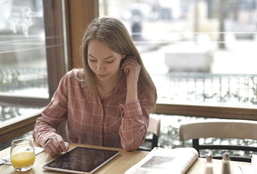 Young woman browsing tablet in cafe