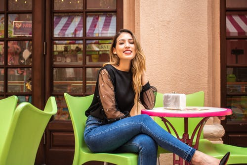 Woman In Black Long Sleeve Top And Blue Denim Jeans Sitting On Green Chair