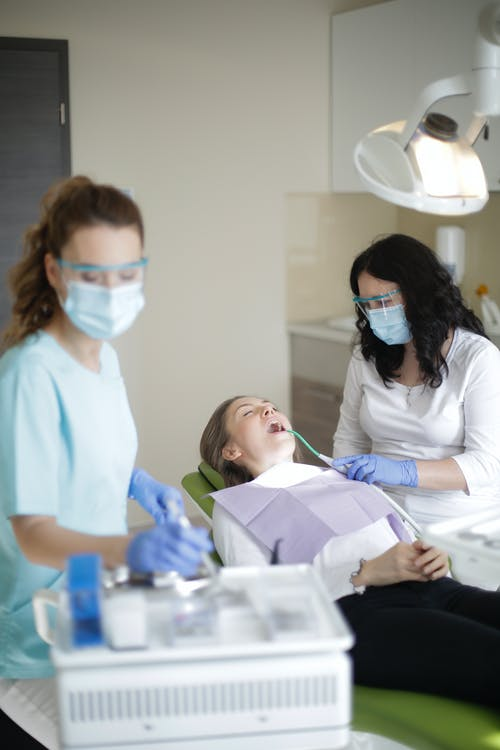 Female dentist with assistant using dental tools and equipment while curing teeth of patient