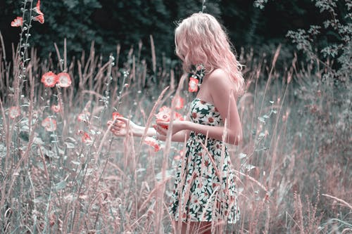 Woman In A Floral Dress Standing On Flower Field
