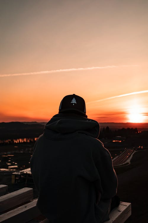 Person Wearing A Hoodie Standing On Top Of A Building During Sunset