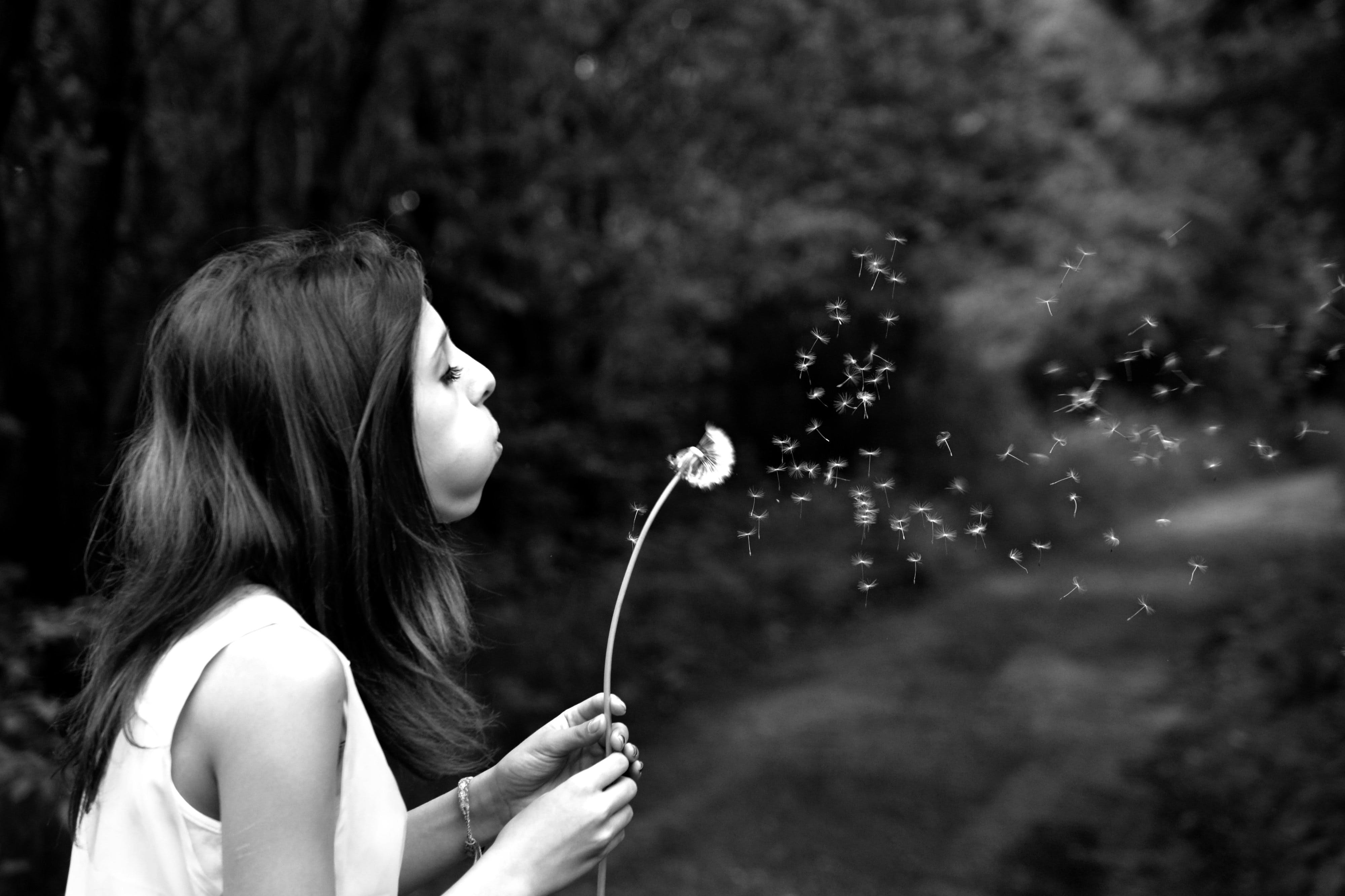 Woman in Tank Top Blowing Dandelion in Grayscale Photography